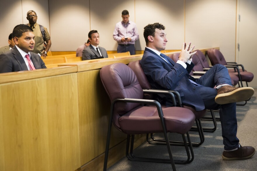 Former Cleveland Browns quarterback Johnny Manziel sits while his defense attorneys confer with the prosecution during his initial hearing in May 2016 in Dallas.
