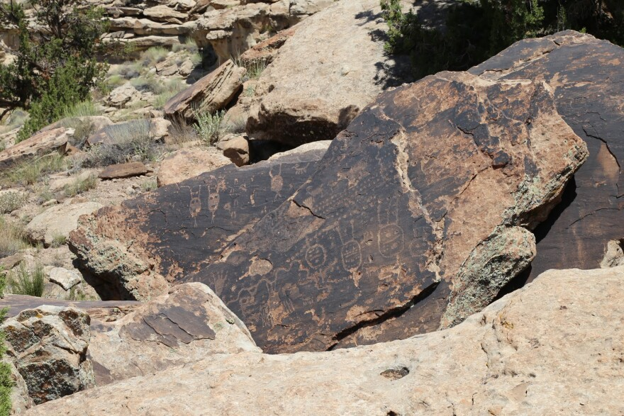 A rock with lots of humanoid figures carved into it.