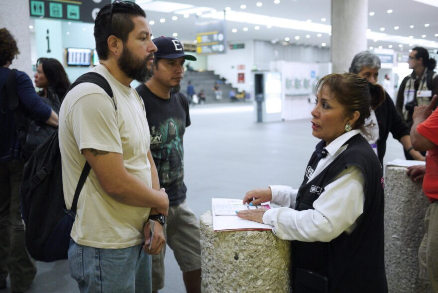 Gustavo Lavariega, a volunteer with Deportees United, talks with an official from Mexico's labor department as he waits for deportees to arrive on a flight from Texas. (Liz Jones/KUOW)