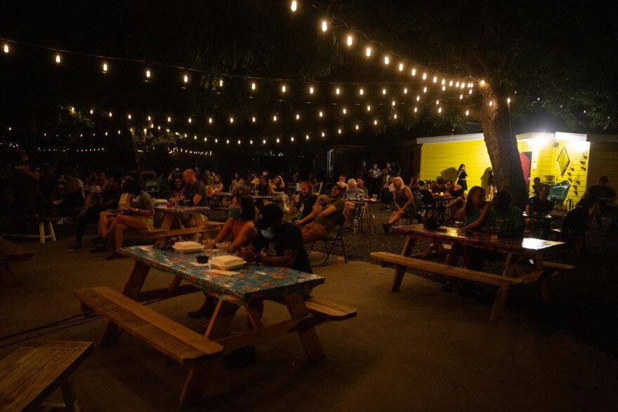 An audience seated a spaced picnic tables watch as musicians and spoken word artists perform at the Far Out Lounge on June 20.