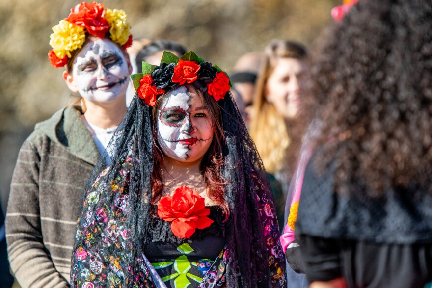 Women with painted faces and floral headbands walk in the parade.