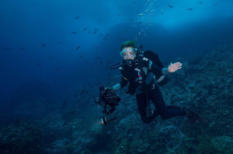 Woman in deep sea diving gear floating beneath ocean surface