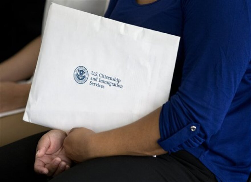 A new citizen holds a package of documents during a U.S. Citizenship and Immigration Services naturalization ceremony on the campus of Florida International University, Monday, July 6, 2015, in Miami.
