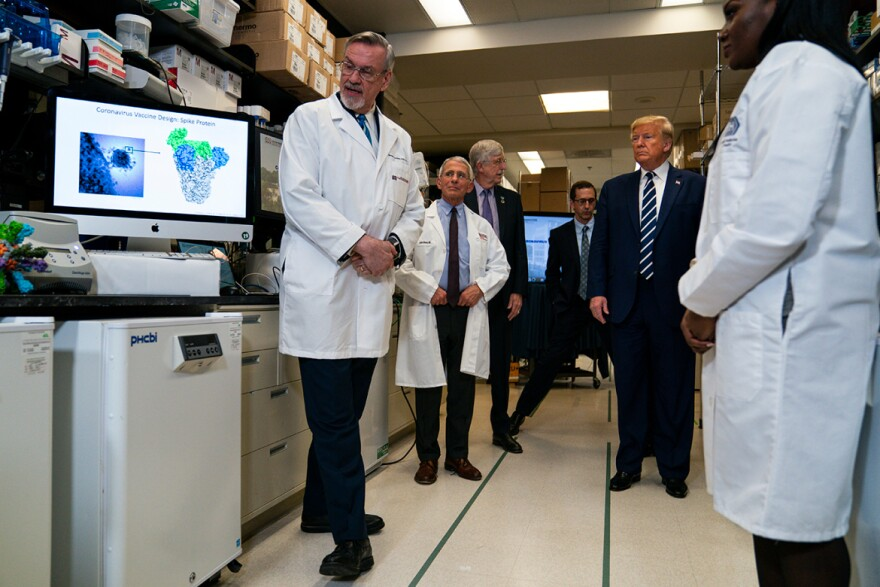 Deputy Director at the Vaccine Research Center at the National Institutes of Health, Dr. Barney Graham, speaks with President Donald Trump during a tour of the Viral Pathogenesis Laboratory at the National Institutes of Health, Tuesday, March 3, 2020, in Bethesda, Md. (AP Photo/Evan Vucci)