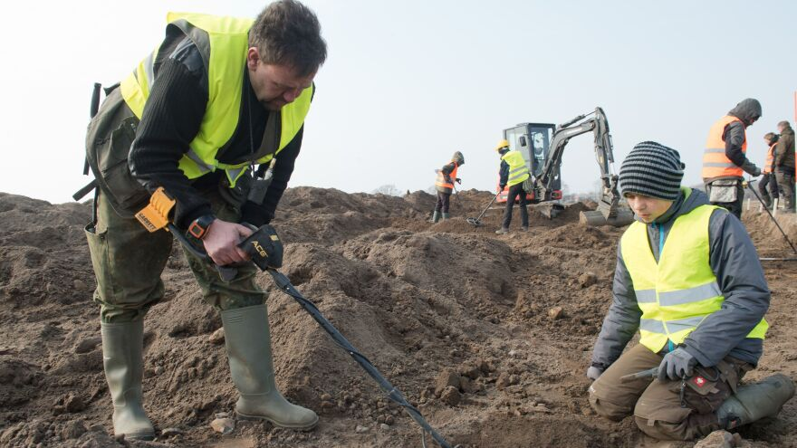 Amateur archaeologist Rene Schoen (left) and 13-year-old student Luca Malaschnichenko look for a treasure with a metal detector in Schaprode, northern Germany, on Friday. The two made their first discovery in January, then participated in a 4,300-square-foot dig that uncovered a larger treasure trove.