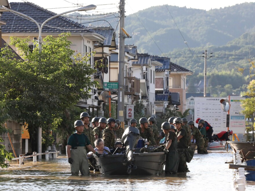 Japan's Self-Defense Forces use boats to rescue people from Mabi Memorial Hospital, which was isolated after flood damage.