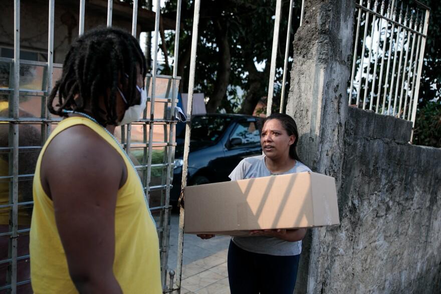 Irani Cristina receives a box of organic food from Dimas Reis through the Pertim program.