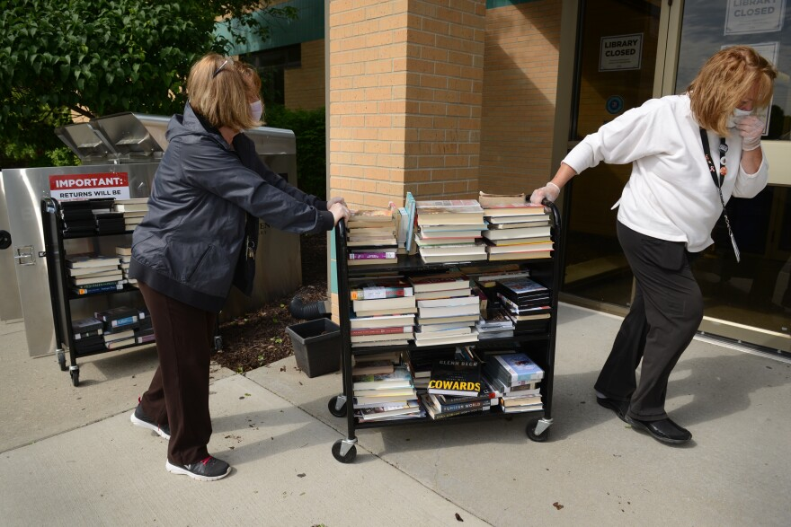 Picture of two women wearing face masks and wheeling a cart of returned library books into the library