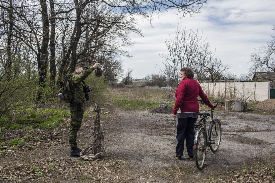 Lt. Mikhail Andronik, a soldier in the Donetsk People's Republic Army, shows an exploded artillery to Vera Anoshina, 52, a local resident.