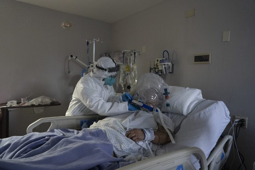 A member of the medical staff treats a patient who is wearing helmet-based ventilator in a COVID-19 intensive care unit in Houston, Texas. (Go Nakamura/Getty Images)