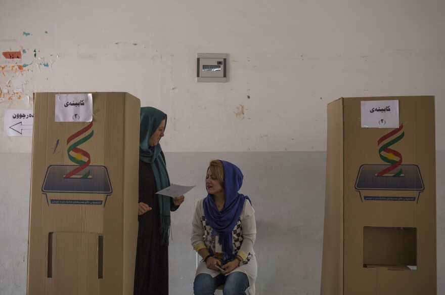 A volunteer looks at a voter's ballot as she walks out of a voting booth on Monday in the disputed city of Kirkuk, Iraq.