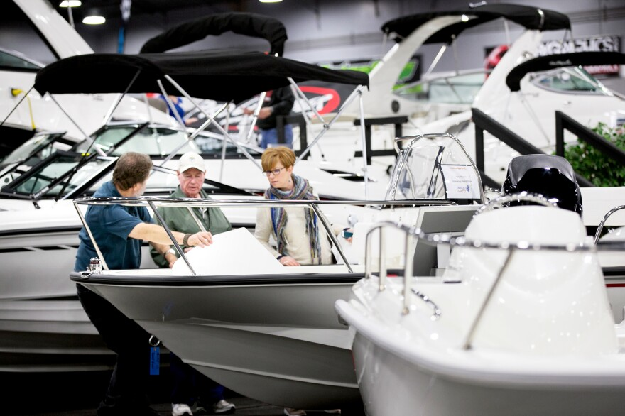 Larry Coleman, a salesman with Trudeau's Marine, talks to Bill Floren and Kimberly Abramski at the 55th Annual Portland Boat Show on Jan. 7 in Oregon. Lower fuel costs are projected to boost boat sales this year.