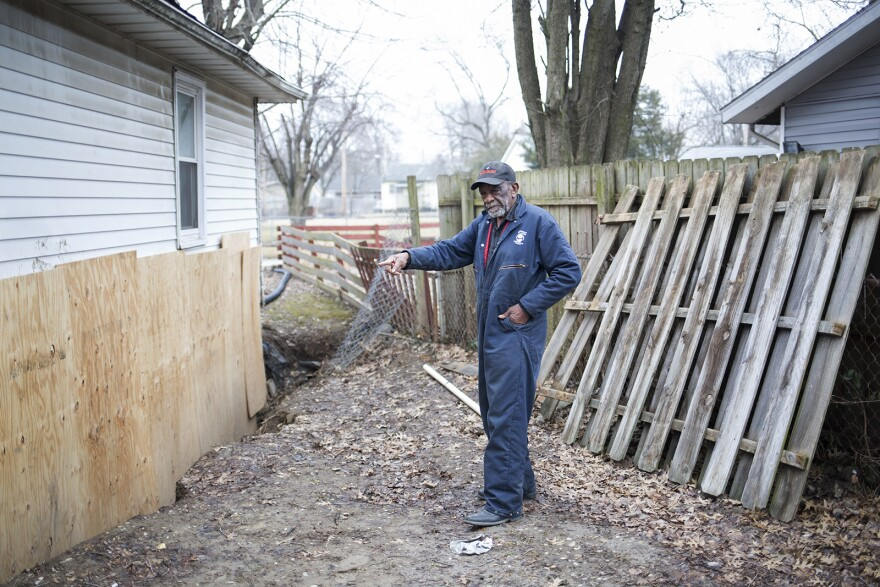 Earlie Fuse points to a plywood wall he constructed after his basement wall collapsed. Jan. 27, 2020