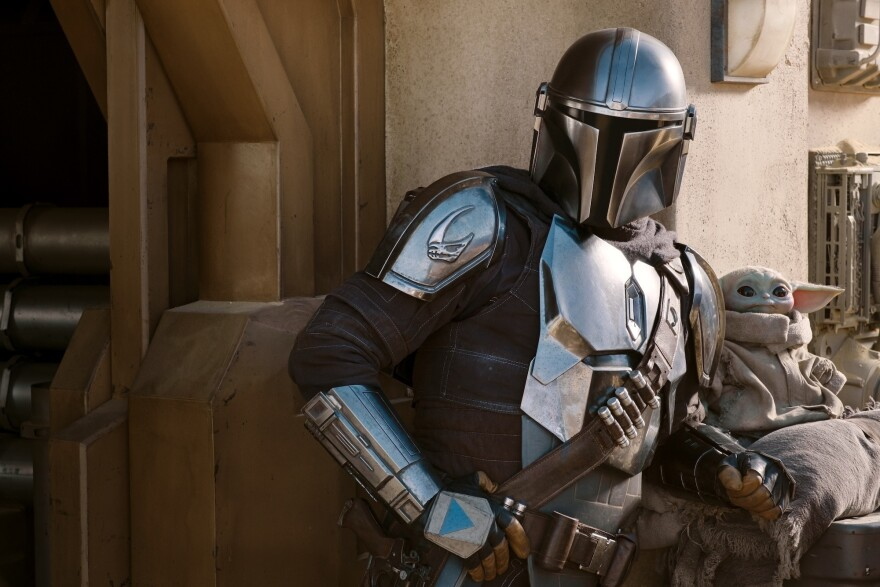 The Mandalorian (Pedro Pascal) and The Child in Season 2 of <em>The Mandalorian on </em>Disney+.