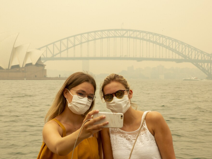 Tourists, wearing face masks due to heavy smoke, take a selfie at Sydney Harbour on Dec. 19, 2019. As news of Australia's wildfires spreads around the world, fewer tourists are arriving in the country.