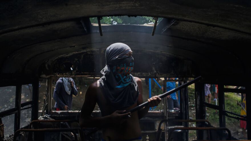 A protester looks around the interior of a burned out bus, which was set alight in Tipitapa during the daylong national strike Thursday.