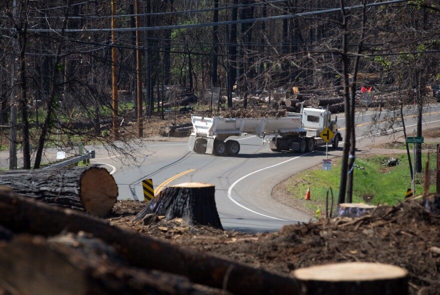 In April, trucks carry tree debris down Clark Road in Paradise, which was heavily forested before the fire.
