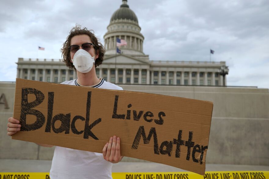 A protester holds a sign in front of the Utah State Capitol building during a protest in Salt Lake City on June 5.