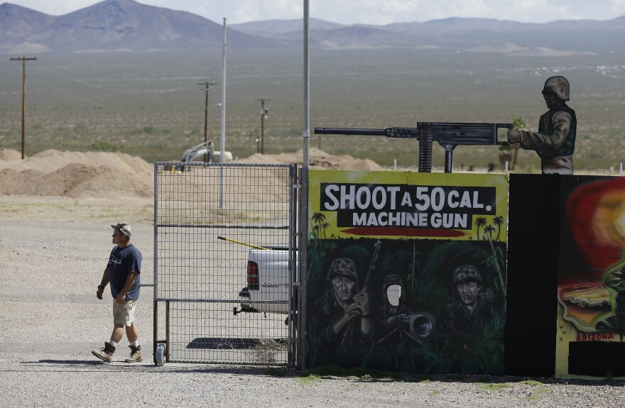 A man closes off an entrance to the Last Stop shooting range in White Hills, Ariz., on Wednesday. Instructor Charles Vacca was killed at the range Monday by a 9-year-old girl he was teaching to use an Uzi submachine gun.
