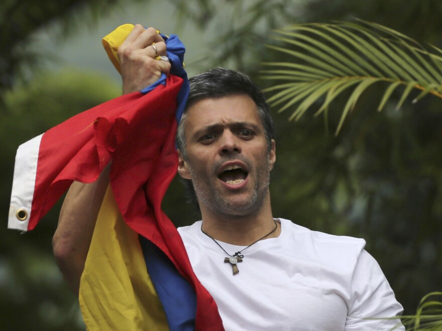 In a photo taken last month, Venezuela's opposition leader Leopoldo Lopez holds a national flag as he greets supporters outside his home in Caracas, Venezuela, following his release from prison and being placed under house arrest after more than three years in military lockup.