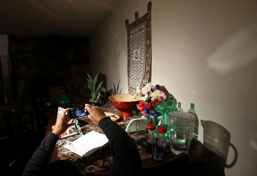 A reporter takes a photo of a dining room table inside the home in Redlands.