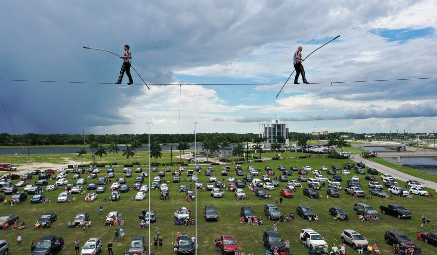 People parked their cars outside in a distanced tailgater in June to watch high-wire artists and cousins Nik (left) and Blake Wallenda perform at Nik Wallenda's Daredevil Rally, billed as the world's first drive-in stunt show at Nathan Benderson Park in Sarasota, Fla.