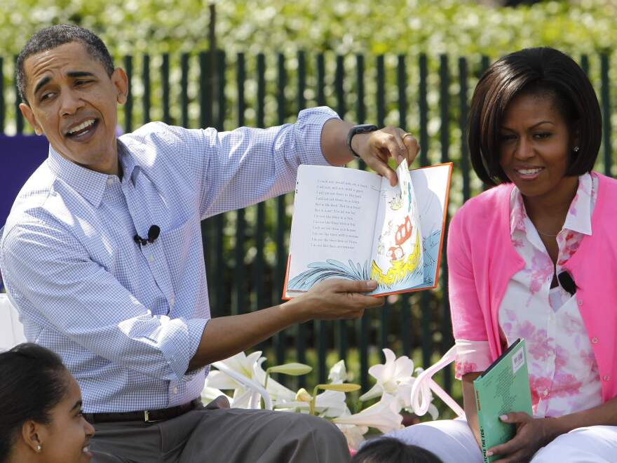 President Obama, accompanied by first lady Michelle Obama, reads <em>Green Eggs and Ham</em> at the annual White House Easter Egg Roll in April 2010.