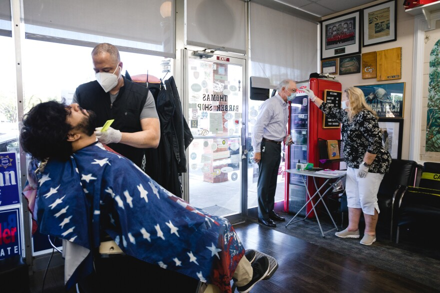 Many counties in Georgia may not have enough hospital beds to treat a new wave of COVID-19 patients, according to internal federal government documents. Above, a barbershop in Atlanta on April 27.