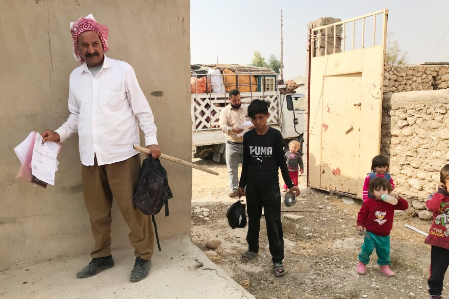 Hassan Murad returns to his damaged home in the village of Wardiya, in Sinjar province, with his wife and five young children. He holds the official documents he needed to return. A teenager from the village helps carry things in.