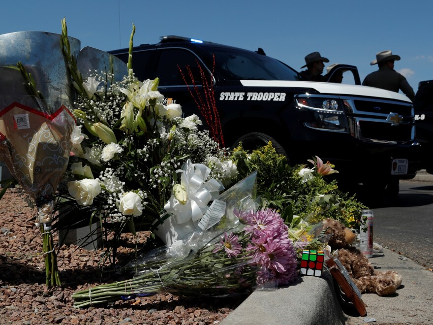 Flowers adorn a makeshift memorial near the scene of a mass shooting at a shopping complex Sunday in El Paso, Texas.