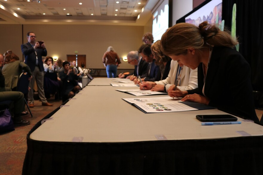 Five people hunch over a table, signing documents.