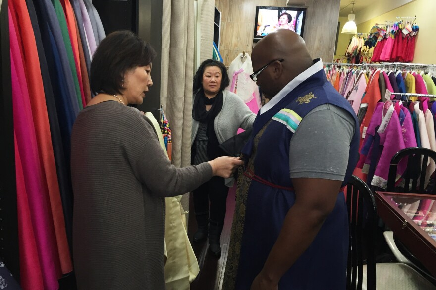 Youjung Jung measures Berris Anderson for a hanbok as his wife Lysa watches.