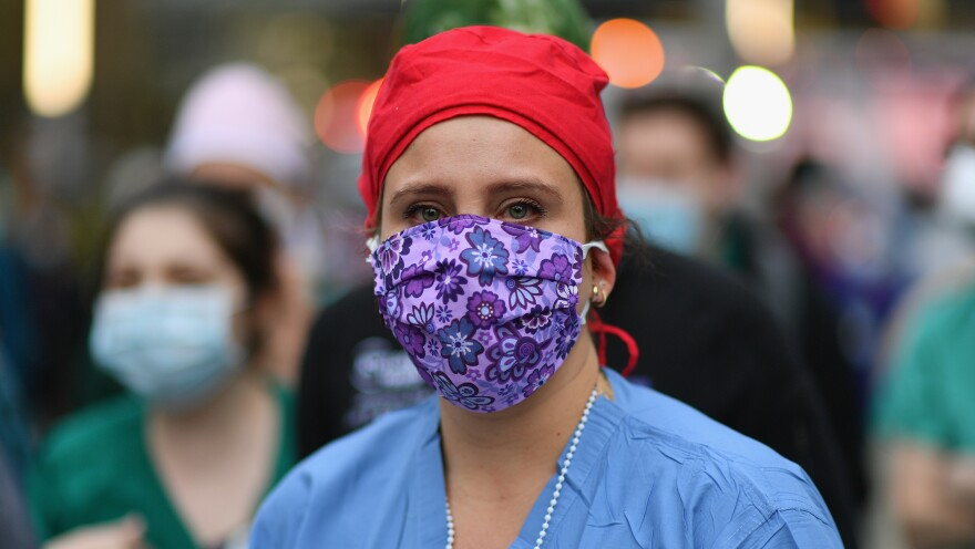A health care worker looks on as people cheer to show their gratitude to medical staff outside NYU Langone Health hospital in New York City last month.