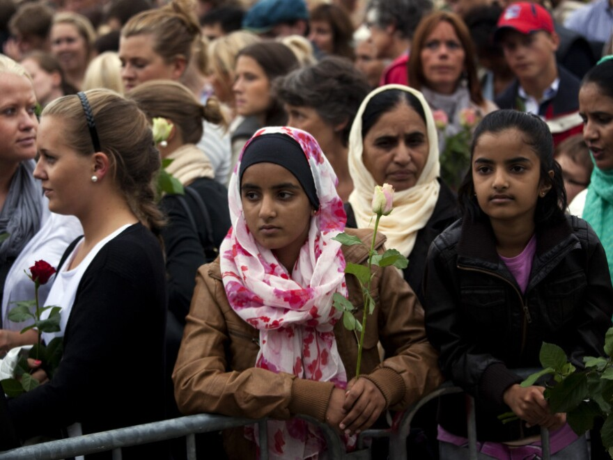 """People gather outside Oslo City Hall on Monday to participate in a """"rose march"""" in memory of the victims of Friday's twin attacks in Norway. Anders Behring Breivik, who admitted to the attacks but entered a plea of not guilty, said he wanted to save Europe from Muslim immigration."""