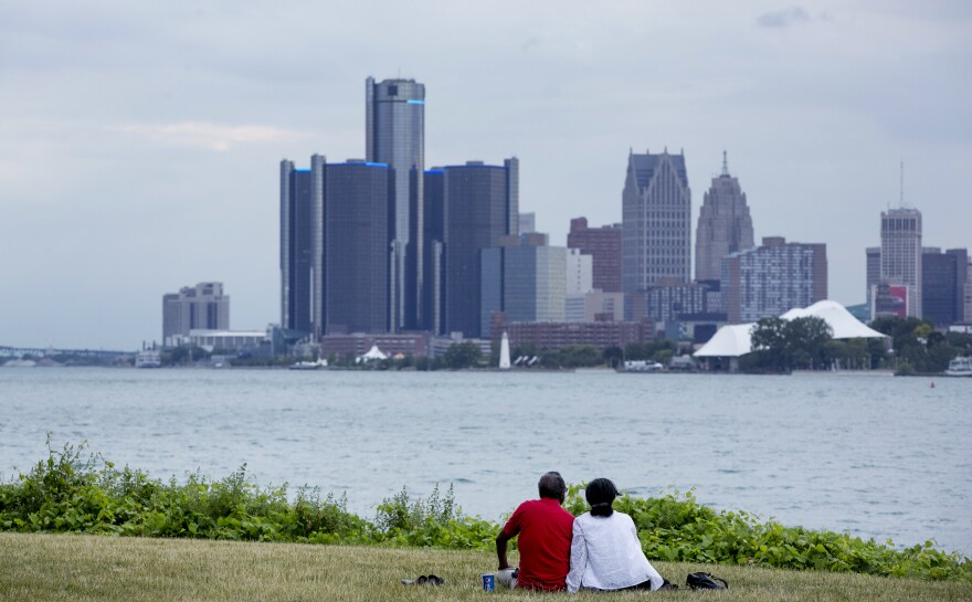 A couple sits on Belle Isle while looking at the skyline in Detroit, Michigan, in 2017. The city has been released from state oversight of its finances after several years of scrutiny.