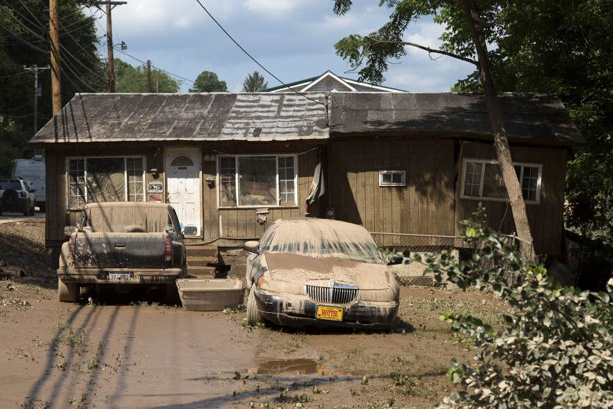 Muddy cars sit in front a flooded-out home on Saturday, June 25, 2016, in Clendenin, in northern Kanawha County, W.Va.