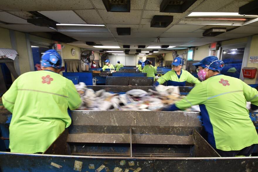 Workers at the Mecklenburg County recycling center try to fish out any bad materials that make it through the sorting machine on fast-moving conveyor belts.