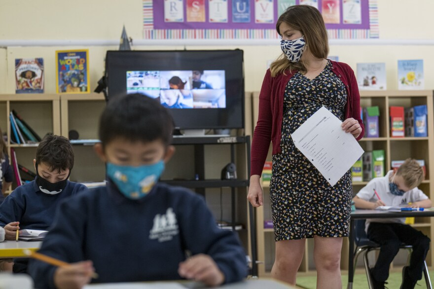 A teacher wearing a protective mask walks around the classroom during a lesson at an elementary school in San Francisco in October 2020.