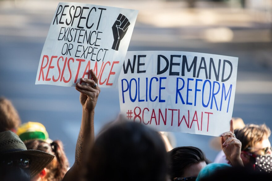 "A protester holds a sign that says ""We demand police reform."""