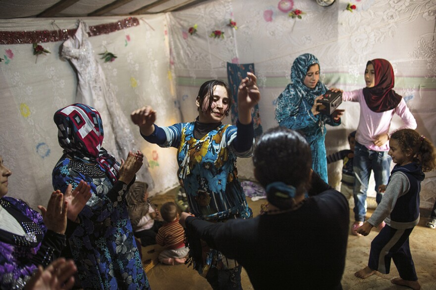 "Syrian refugees dance at a wedding celebration in a refugee camp in Marj El-Khokh, in Marjaayoun, Syria. The father of the groom said, ""We want to create life out of death .... People should not continue to be morbid."" March 2014"