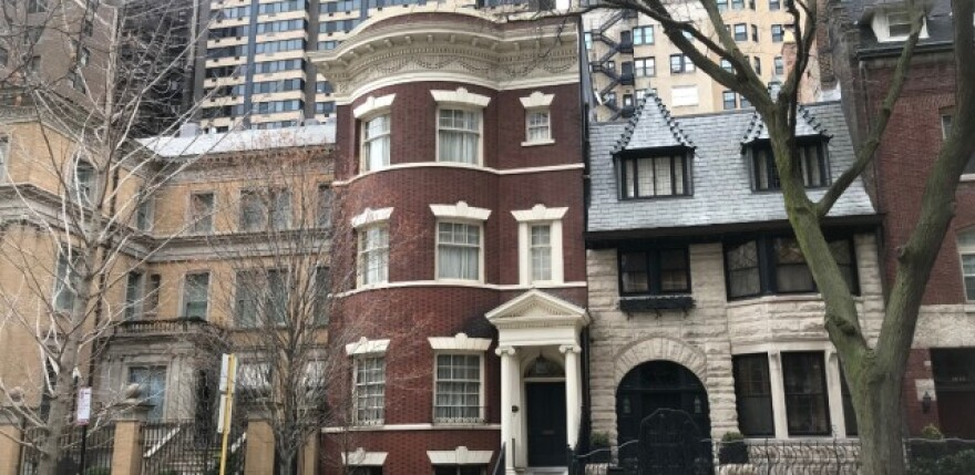 Illinois Gov. JB Pritzker and his wife, First Lady MK Pritzker, purchased a tan mansion (left) and red brick home (center) more than a decade ago in Chicago's upscale Gold Coast neighborhood. WBEZ has learned the federal government is investigating the Pr
