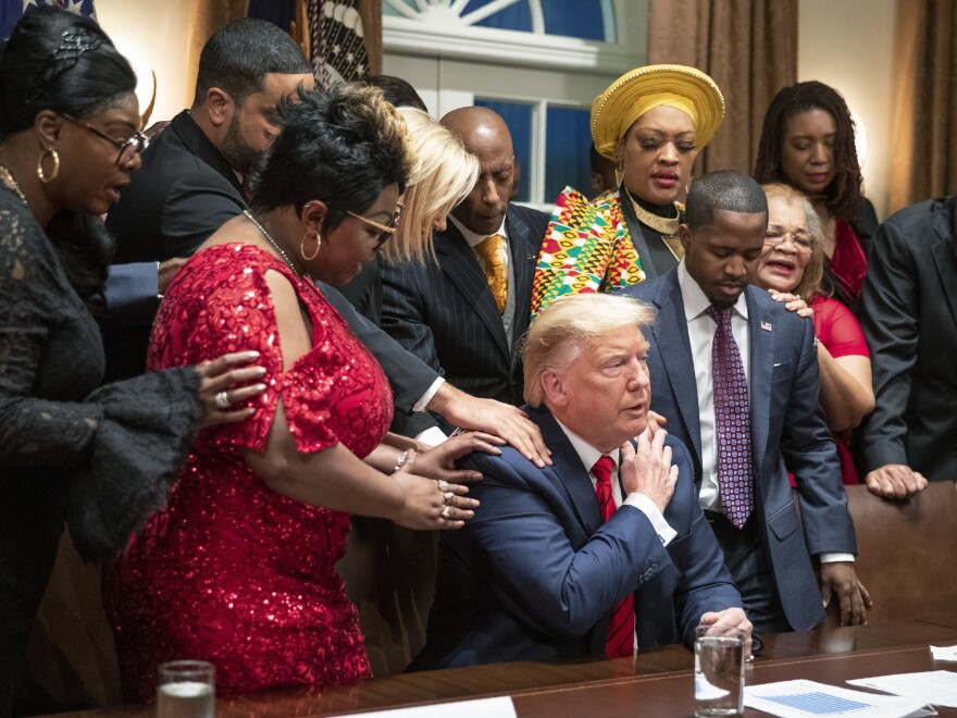 Black leaders say a prayer with President Trump as they end a meeting in the Cabinet Room of the White House in February.