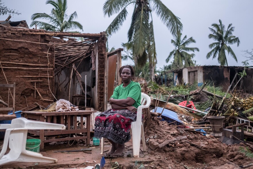 Tamazina Carlos sits outside what remains of her house. The school assistant escaped just before the ceiling caved in. Since the cyclone hit on Thursday, she has been sleeping under a pile of palm fronds.