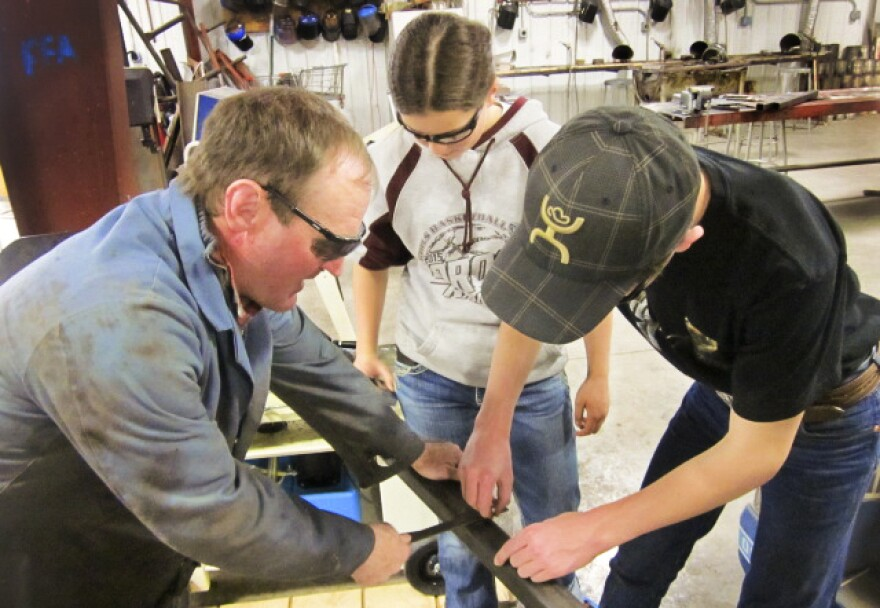Whaley and students use a T square before they cut a piece of steel for their bale feeder.