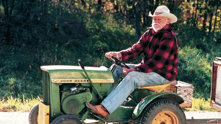 Richard Farnsworth on top of a John Deere riding lawnmower.