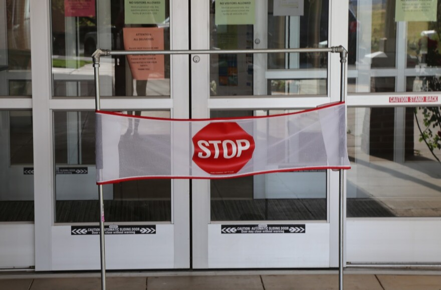 """A sign in front of glass doors says """"stop"""""""