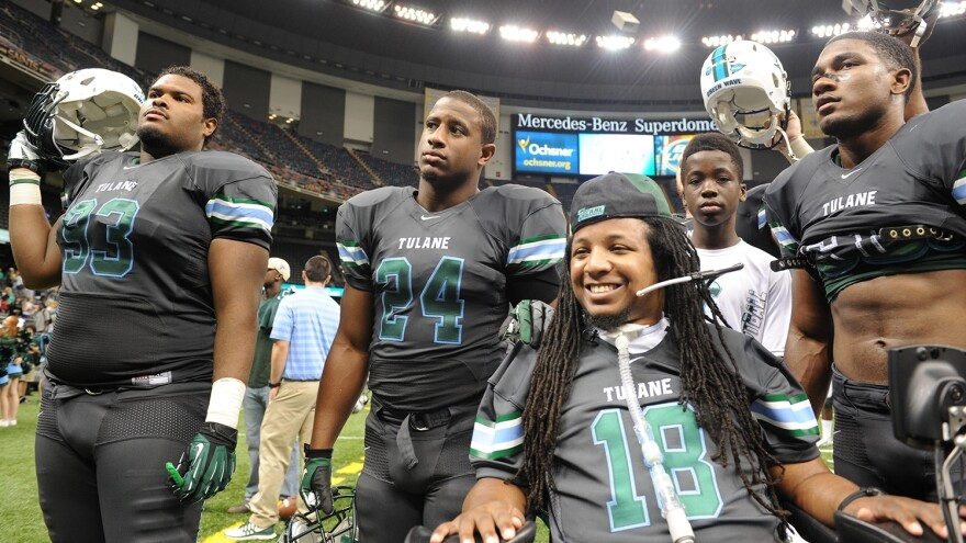 Devon Walker smiles with his teammates after the school's home opener in New Orleans. A former team captain, Walker was paralyzed from the waist down during a tackle last September.
