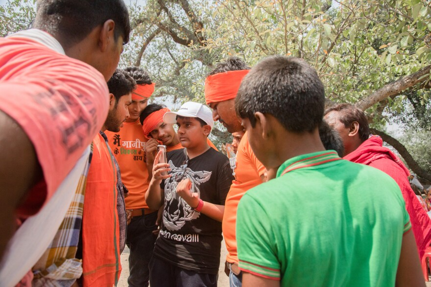 Rian Narvekar (center, in white hat), 13, interacts with local boys his age while on an election-themed tour of Uttar Pradesh state. Rian's father took him on this tour to understand politics in India's rural heartland.