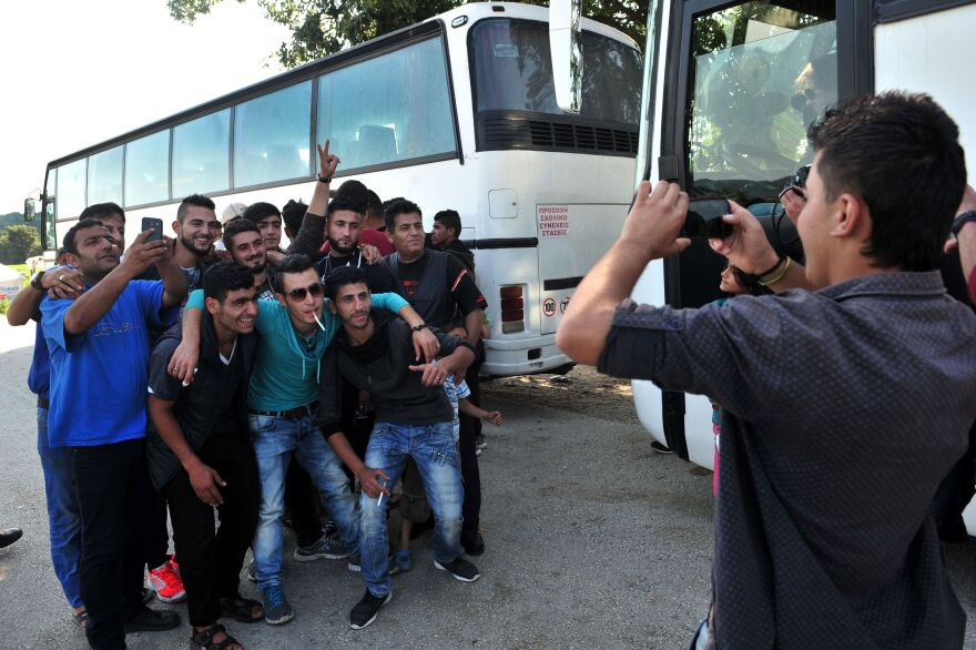 Men pose for a photo on Monday as some of them prepare to leave the squalid camp.