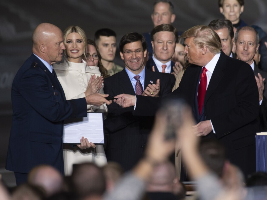 President Trump gives the pen used to sign a copy of the National Defense Authorization Act for fiscal year 2020 to the U.S. Space Force's first chief of space operations, Gen. John Raymond, on Dec. 20.